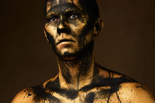 Man Covered With Gold Paint And Black Crude Oil Color.