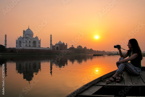 Photo Woman watching sunset over Taj Mahal from a boat, Agra, India