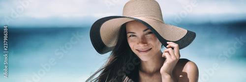 Beach sun tan skin care Asian beauty woman happy on beach vacation panoramic banner wearing sunhat. Healthy suntan skincare concept with hat.