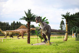 Park of dinosaurs. A dinosaur on the background of nature. Toy dinosaurs in the amusement park.
