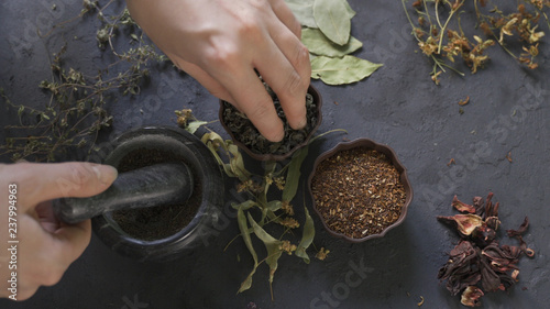 Foto  Herbal medicine preparation with fresh herbs and flowers, aromatherapy essential oil, mortar with pestle and scissors on hemp paper background