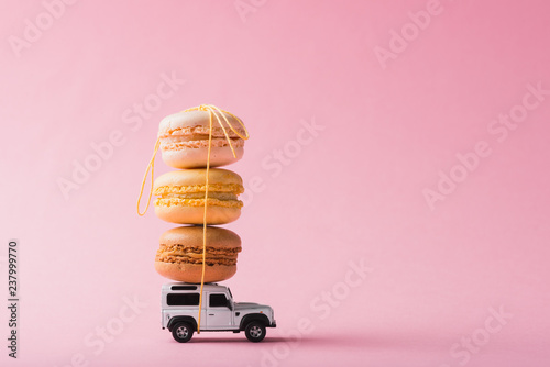 Poster Macarons Macaron cookies on top of a toy car over pink background