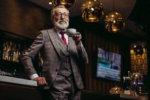 Portrait Of Wealthy Prosperious Senior Businessman In Drinking Coffee Near Bar Counter At Elite Gentlemen Club