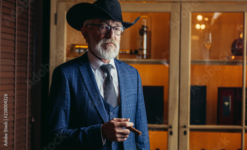 Thoughtful, selective, male aged investor in glasses, smoking cigar, fume, hold Canvas
