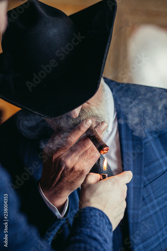 Stylish old-aged man in wide brimmed hat and rich dark blue mens suit lights a cigar indoor, standing near the bar counter with alcohol drinks Canvas