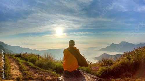 Fotografia Monk sitdown on the rock with sunset.