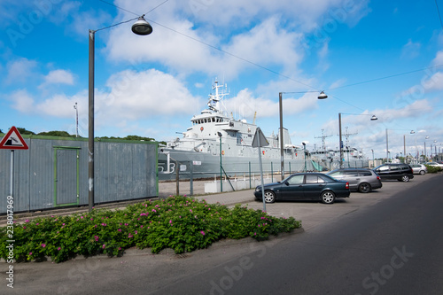 Street in Liepaja near sea port. Battleships in the dock Fotobehang