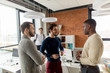 Successful mixed race hipster male team in coworking space. Freelancers cooperate working in open space modern office