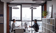 canvas print picture Image of two young Indian and Asian colleagues interacting, sitting opposite each other in office with big panoramic window