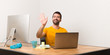 Man working with laptot in a office saluting with hand with happy expression