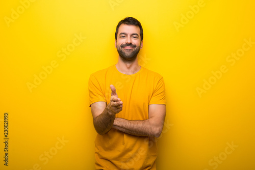 Fotografie, Obraz  Man on isolated vibrant yellow color shaking hands for closing a good deal