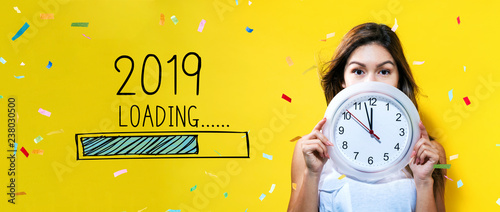 Photo  Loading new year 2019 with young woman holding a clock showing nearly 12