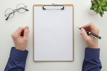 Clipboard With Attached Blank White Sheet. Man Hands Holds Pen On White Background With Green Plant And Eyeglasses. Flat Lay Mockup Business Document Concept