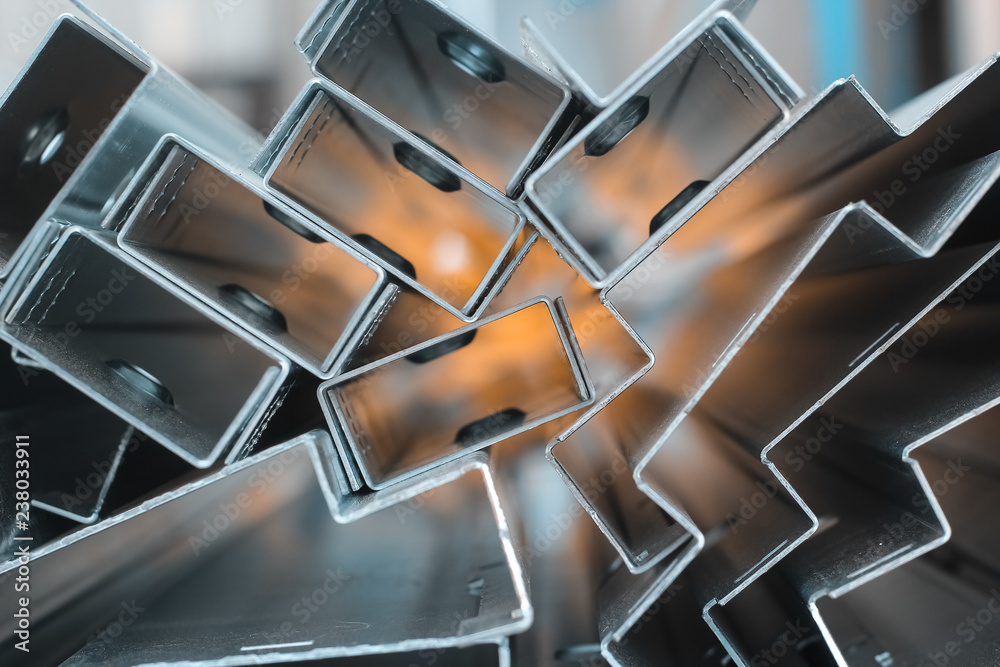 Fototapety, obrazy: Focused Blurred Background for steel sheet metal profiles. a Stell Zinc coated profiles in the rack in artistic blurry organe background. In focus version