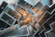 Focused Blurred Background For Steel Sheet Metal Profiles. A Stell Zinc Coated Profiles In The Rack In Artistic Blurry Organe Background. In Focus Version