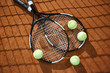 View of two new tennis rackets and several balls on court that can be used as background