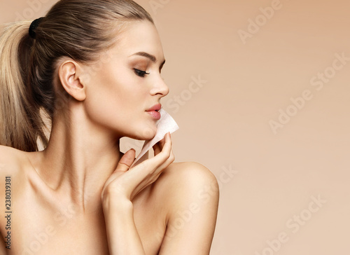 Obraz Woman cleaning face with facial cleansing wipes, removing makeup. Photo of woman with perfect skin on beige background. Beauty concept - fototapety do salonu