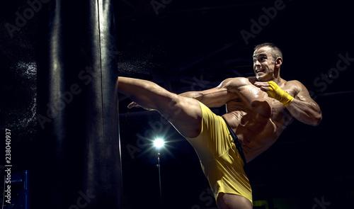 Photo  Thai boxer punch kick by punching bag