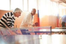 Two Senior Active Men With Rackets Trying To Catch Ping Pong Ball During Leisure Game