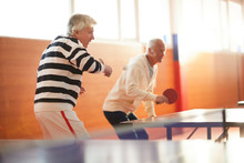 Two Active Senior Men With Rackets Attacking Ping Pong Ball While Standing By Tennis Table During Game