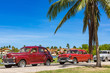 Amerikanischer roter und braun-roter Oldtimer parken am Strand unter Palmen in Havanna Kuba - Serie Kuba Reportage