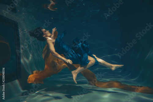 Poster Chambre d enfant cute sporty female swims underwater as a free diver in a blue evening dress with orange fabric alone