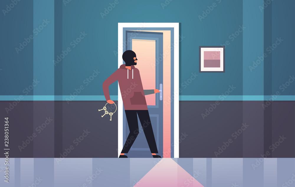 Fototapeta burglar in black mask using bunch skeleton keys breaking entering into home criminal thief character open door night house interior flat horizontal