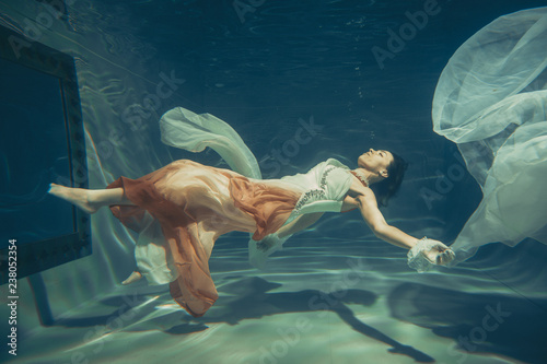 Poster Chambre d enfant elegant slender girl swims underwater like a free diver in a white evening dress with beautiful fabric