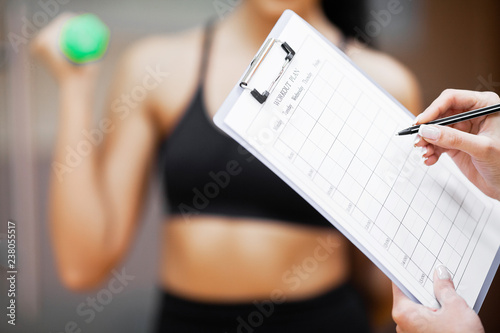 Fitness plan. Sports trainer amounts to workout plan close-up Fototapeta