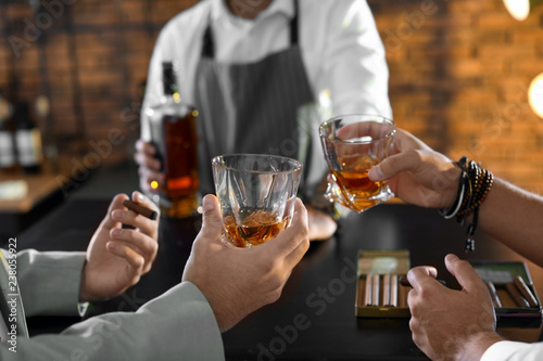 Fotografie, Tablou Friends drinking whiskey together in bar, closeup