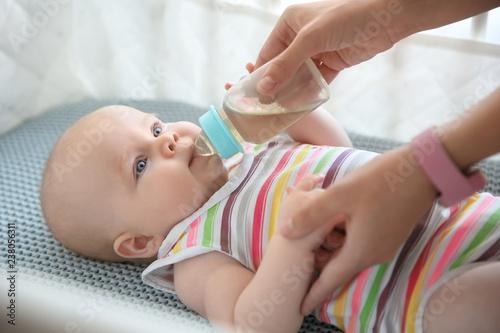 Fototapeta Lovely mother giving her baby drink from bottle in cot obraz na płótnie