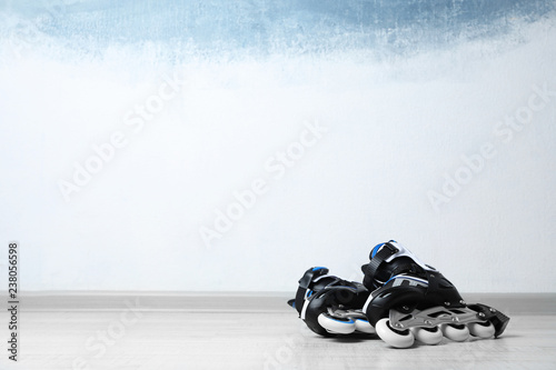 Inline roller skates on floor near color wall. Space for text