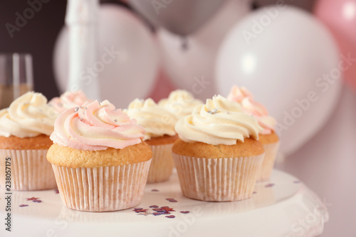Photo  Stand with cupcakes and blurred balloons on background, closeup