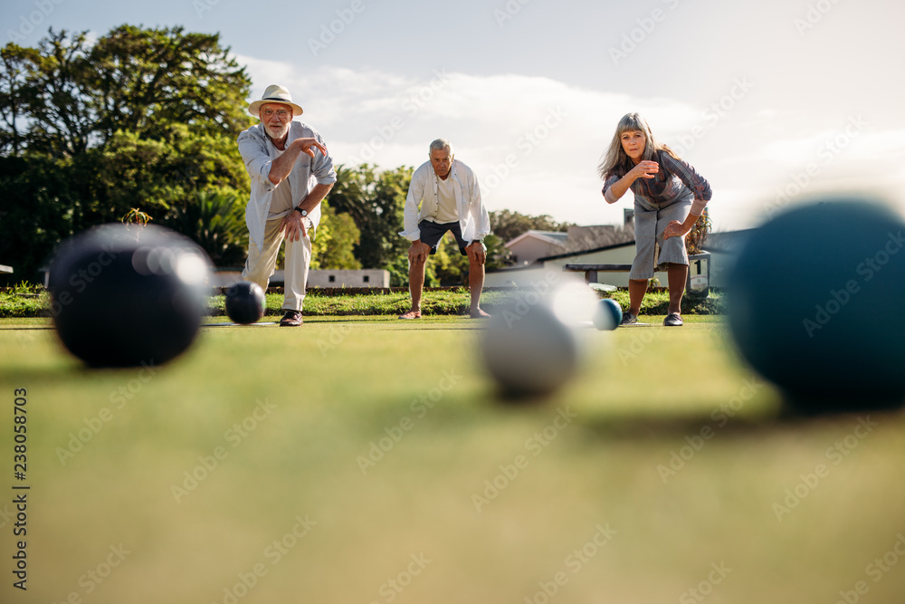 Fototapety, obrazy: Senior people playing boules in a park