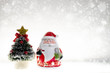 Red Santa Claus Doll on Blurred Bokeh Snow Background with Copy Space for Montage or Display Design Text and Advertising