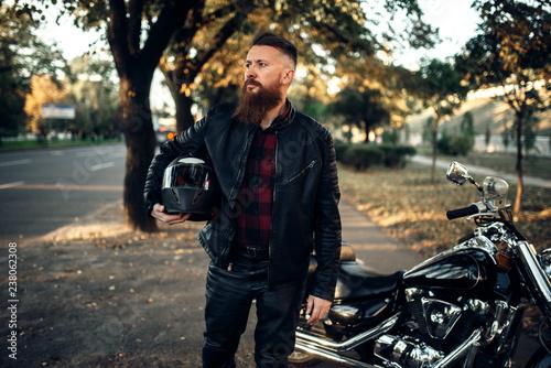 Biker in leather jacket near black chopper Fotobehang