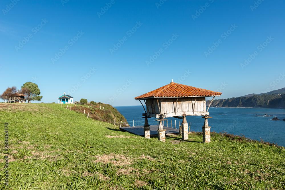 Fototapety, obrazy: Typical granary (horreo) and the chapel of La Regalina in Cadavedo, Asturias, Spain