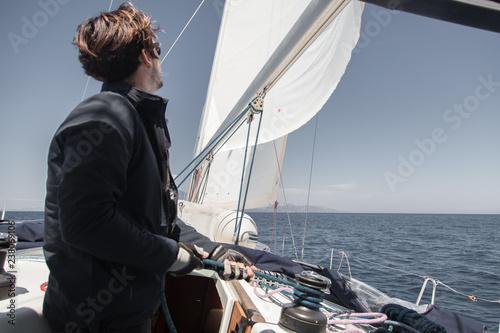 Sailor sets sail on a sailing yacht. - 238069106