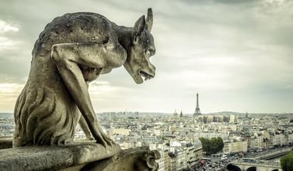 Gargoyle on the Cathedral of Notre Dame de Paris looks at the Eiffel Tower, Paris, France