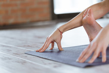Close-up Of Feet And Hands Of Attractive Sporty Young Woman Practicing Yoga Indoor On Wooden Floor On Fitness Mat. Beautiful Fitness Girl Doing Yoga Asana In Loft Class. Healthy Lifestyle