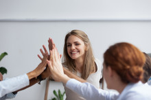 Diverse Multinational Businessmen And Businesswomen Gathered Together In Boardroom Before Seminar Giving High Five Expressing Respect Team Spirit And Unity, Focus On Attractive Happy Millennial Female