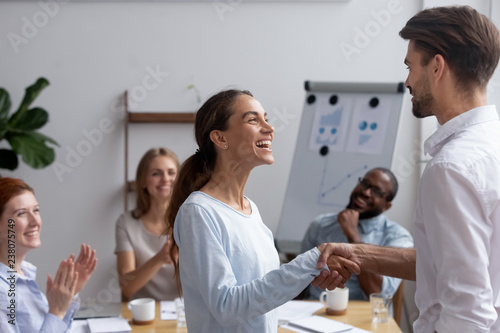 Fotografie, Obraz  Excited mixed race girl employee get promotion feels happy handshaking with executive manager or company boss