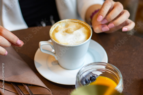 Garden Poster Tea Brown table with fresh cappuccino coffe in a white cup, fruit dessert and young woman's hands- close up
