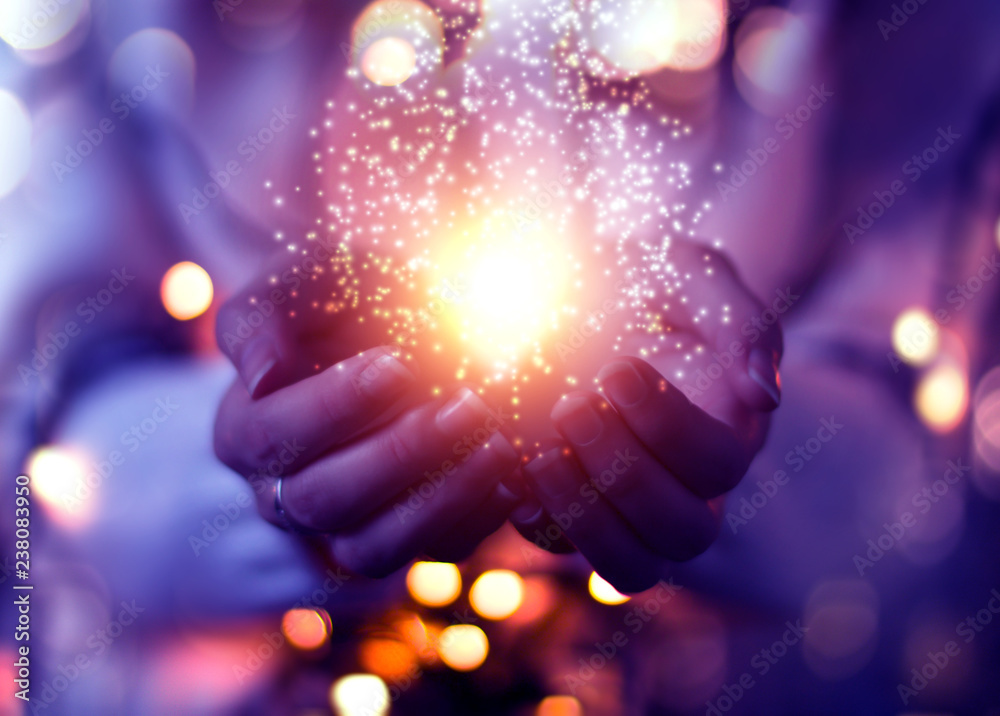 Fototapeta Magic particles emanating from female hands. Christmas background with bokeh