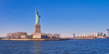 Fototapeta New York - Vista desde el rio Hudson, al atardecer, de la estatua de la libertadla isla de la libertad y el horizonte de Manhattan , donde numerosos turistas, van a visitarla cada dia,desde Manhattan.