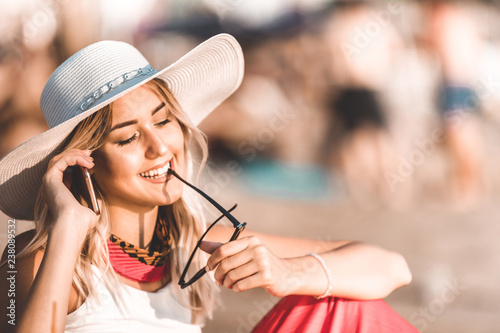 Fotografia Attractive girl talking on a mobile phone on the beach
