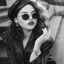 Monochrome Close Up Fashion Portrait Of Young Beautiful Fashionable Girl Wearing Trendy Sunglasses, Wrist Watch, Earrings, Leather Beret, Checkered Dress, Posing In Street, Sitting On Stairs