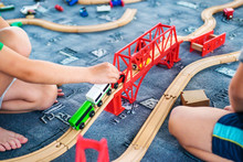 Child Play With Wooden Train, Build Toy Railroad At Home Or Kindergarten. Toddler Kid Play With Wooden Train