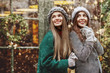canvas print picture - Outdoor portrait of two young beautiful fashionable happy smiling surprised girls posing at festive Cristmas fair. Models looking up, wearing stylish winter clothes. Copy, empty space for text