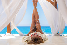 Beautiful Young Woman Lying On A Cabana With Her Feet In The Air